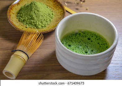 Matcha green tea in traditional ceramic chawan (tea bowl) with bamboo whisk and traditional bamboo tea spoon on the wooden tray