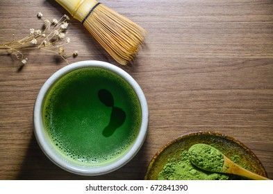 Matcha green tea in  traditional ceramic chawan (tea bowl) with bamboo tea whisk and green tea powder in ceramic plate on the wooden tray