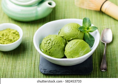 Matcha ice cream scoop in white bowl on a wooden background.