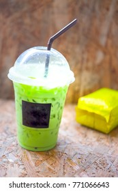 Matcha iced green tea in clear plastic glass on wooden background