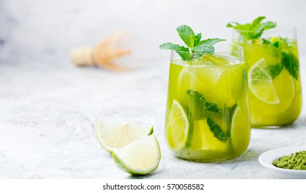 Matcha iced green tea with lime and fresh mint on a marble background Copy space.