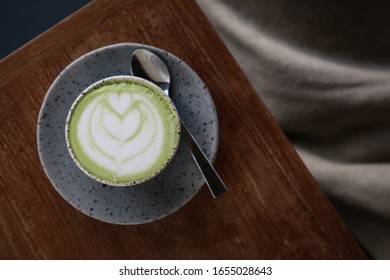 Matcha latte with latte art on topon a wooden background, top view