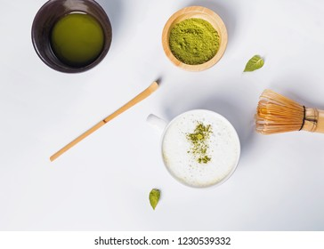 Matcha latte in a cup, powder and tools for making tea on the white background, top view
