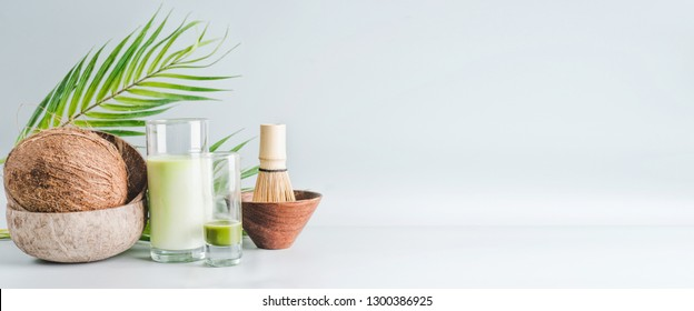 Matcha latte drink with coconut milk on table with whole coconut , matcha espresso and macha whisk, front view, banner. Healthy detox nutrition, vegan food and clean eating concept. Copy space, banner