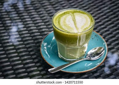 Matcha latte in glass on table in cafe closeup