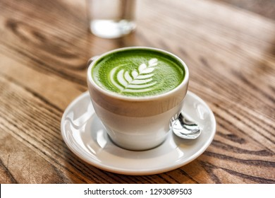 Matcha latte green milk foam cup on wood table at cafe. Trendy powered tea trend from Japan.