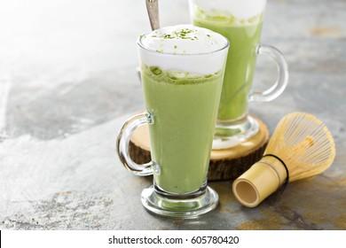 Matcha latte with milk foam in tall glasses