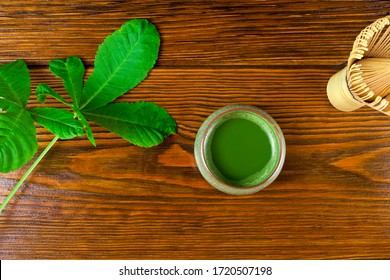 Matcha tea in a cup and green leaves with bamboo matcha tea whisk also know as chasen on a wooden background. Top view.