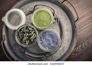 Matcha tea powder, blue matcha powder and organic dried pea flowers (anchan tea) in jars on wooden background, top view