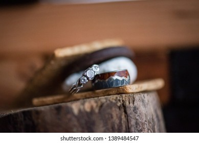 Matched set of wedding rings, a womans diamond engagement ring along with a mens custom mountain with wood inlay wedding band sitting in a s'more campfire setting outdoors on wood