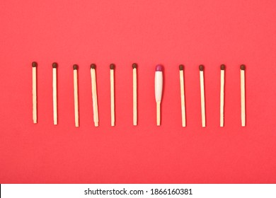 matches are arranged in a row on a red background, one waterproof match among simple matches top view