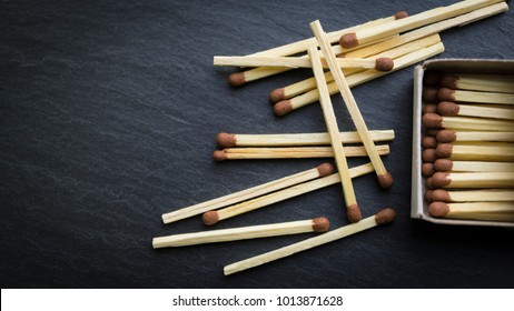 Matches in box, dark background. Macro photography. Close-up shot. Matches in open match-box on carton underlay.
