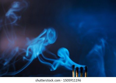 Matches just extinguished in a mystical dark blue light against a dark background. Spectacular smoke. Minimalism, place for text.