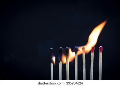 Matches On Fire/ a row of matchsticks burning is sequence from left to right showing connection and sharing