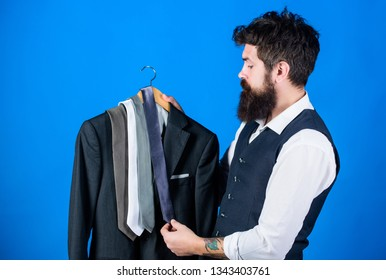 Matching necktie with outfit. Man bearded hipster hold neckties and formal suit. Guy choosing necktie. Perfect necktie. Shopping concept. Shop assistant or personal stylist service. Stylist advice.