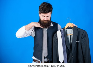Matching necktie outfit. Man bearded hipster hold neckties and formal suit. Perfect necktie. Shopping concept. Stylist advice. Difficulty choosing necktie. Shop assistant or personal stylist service.