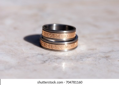 Matching titanium and rose gold wedding bands with engraved dates
