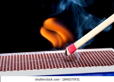 A matchstick lights after it is struck agains the flint surface of a match box.  Everything is real, no flame filters.