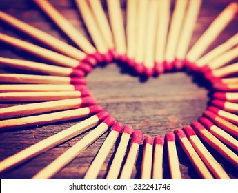 matchsticks in the shape of a heart toned with a warm retro vintage instagram filter effect