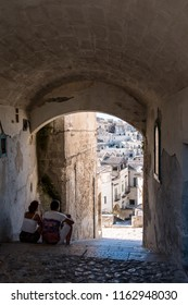 Matera, Basilicata, Italy - July 2018 - Young couple see the landscape of old town of Matera through the archway,  Matera is an European Capital of Culture for 2019, UNESCO World Heritage