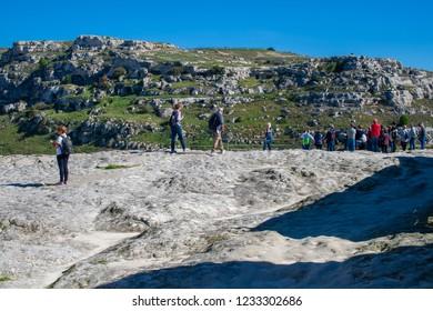 Matera, Basilicata / Italy - October 26 2018: Tourists on the rocks looking at the canyon of Sassi or stones of Matera European capital of culture 2019, Basilicata, Italy