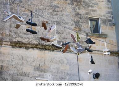 Matera, Basilicata / Italy - October 26 2018: Shoes hanging. Sassi or stones of Matera European capital of culture 2019, Basilicata, Italy