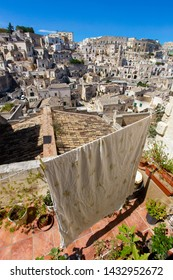 Matera, Basilicata/Italy - September 01 2013: Bed sheet  hanging on a terrace of a stone house  with the stunning view of the ancient town of Matera, european capital of culture 2019.