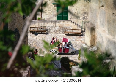 """Matera, Basilicata/Italy - september 01  2013: Tourists taking picture during an Ape tour of the ancient stone city of Matera, on top of an italian characteristic means of transport  """"Ape Calessino""""."""