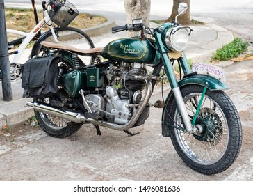 Matera, Italy - 3 September 2019: Historic British motorcycle Royal Enfield green colour parked in a street in the city of Matera, front side view.