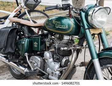 Matera, Italy - 3 September 2019: Historic British motorcycle Royal Enfield green color parked in a street in the city of Matera, close-up shot.