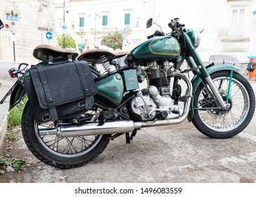 Matera, Italy - 3 September 2019: Historic British motorcycle Royal Enfield green colour parked in a street in the city of Matera, rear side view.