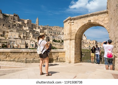 Matera, Italy - August 18, 2018: Tourists take selfies and snapshots with the background of Matera in a sunny day