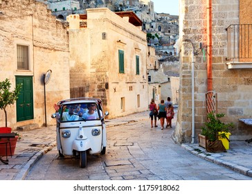 MATERA, ITALY - JULY 2017: A white Ape Piaggio driving down a street and tourists walking by.