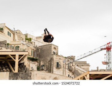 """Matera, Italy - October 5, 2019: Edward Scott performs a stunt jump between two platforms during the final of Red Bull's """"Art of Motion""""."""