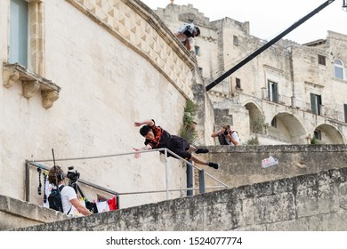 """Matera, Italy - October 5, 2019: Montree Bouwdok performs a stunt jump in the air during the final of Red Bull's """"Art of Motion""""."""