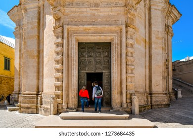 Matera, Italy - September 23 2018: A young tourist couple enter the medieval Chiesa del Purgatorio church in Matera, Italy