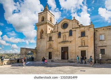 Matera, Italy - September 28 2018: Tourists, mothers and daughters pass by the facade of the Church of San Pietro Caveoso with the ancient sassi caves in the distance on a summer day in Matera, Italy