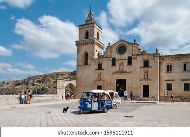 """Matera, Italy - September 6, 2019: Piaggio """"Ape"""" 3-wheeler taxi on San Pietro Caveoso church waiting to pick tourists for tour on stone city of Sassi"""