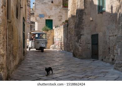 "Matera, Italy - September 9, 2019: Piaggio ""Ape"" 3-wheeler taxi on Via Fiorentini at heart of Sassi Di Matera and a cat crossing the stone street"