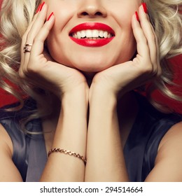 Material girl and femme fatale concept. Marilyn Monroe, Madonna style. Close up portrait of rich young woman smiling wearing expensive luxurious golden ring, bracelet. Perfect shiny smile. Studio shot