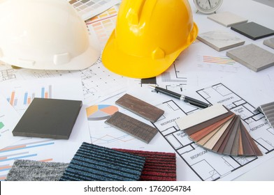 Materials construction. Home materials for Engineer and architec. Safety helmet on work table. Home budget and plan with materials design. Sample of wood laminate and carpet.