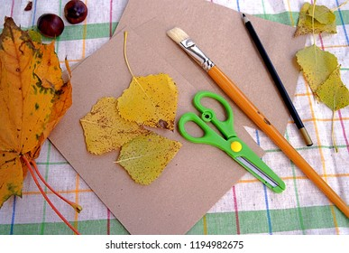Materials for creating thematic autumn children's crafts: leaves, scissors, chestnut , a brush, kraft paper, a pencil.
