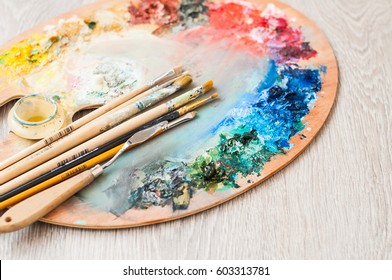 Materials for creativity, palette and brush for painting on a wooden background. The concept of fine art.