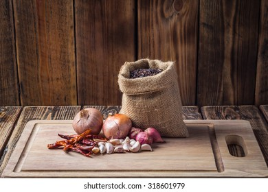 Materials used for cooking in the kitchen have rice, pepper, garlic, onion on cutting board.