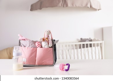 Maternity bag with baby accessories on table indoors. Space for text