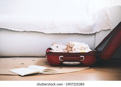 Maternity bag for hospital and paper diary with checking list at home interior. Suitcase of baby clothes and necessities preparing for newborn birth during pregnancy.