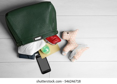 Maternity concept. Female handbag with baby things and cellphone on white wooden background