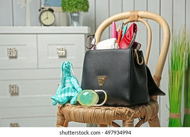 Maternity concept. Female handbag full of different things on wicker chair in the room