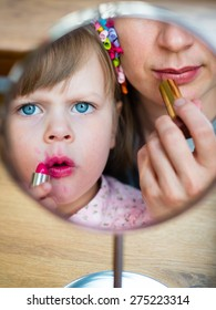 Maternity - Little girl imitating her mother who is applying lipstick in front of small makeup mirror. Girl with big blue eyes