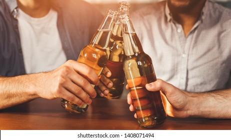 Mates Clinking Bottles Of Beer, Having Rest In Pub